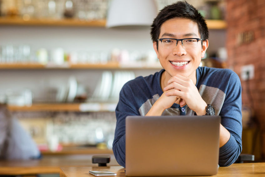 48788794 - portrait of positive asian male in glasses with laptop in cafe